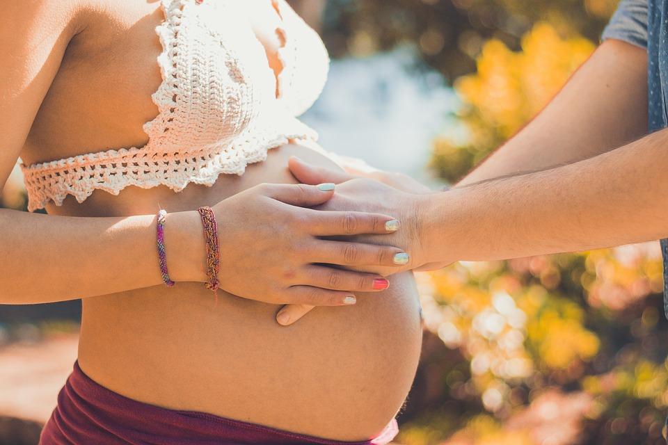 Мужчина прикасается в животу беременной женщины