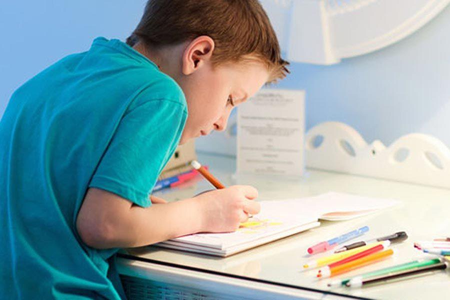 Мальчик рисует за столом