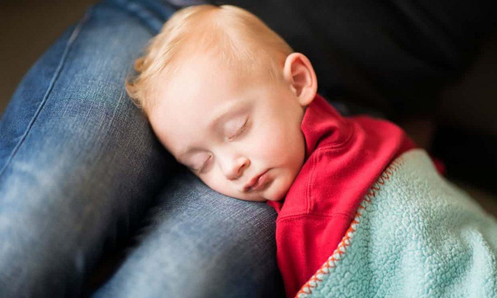 Ребенок спит на коленях матери
