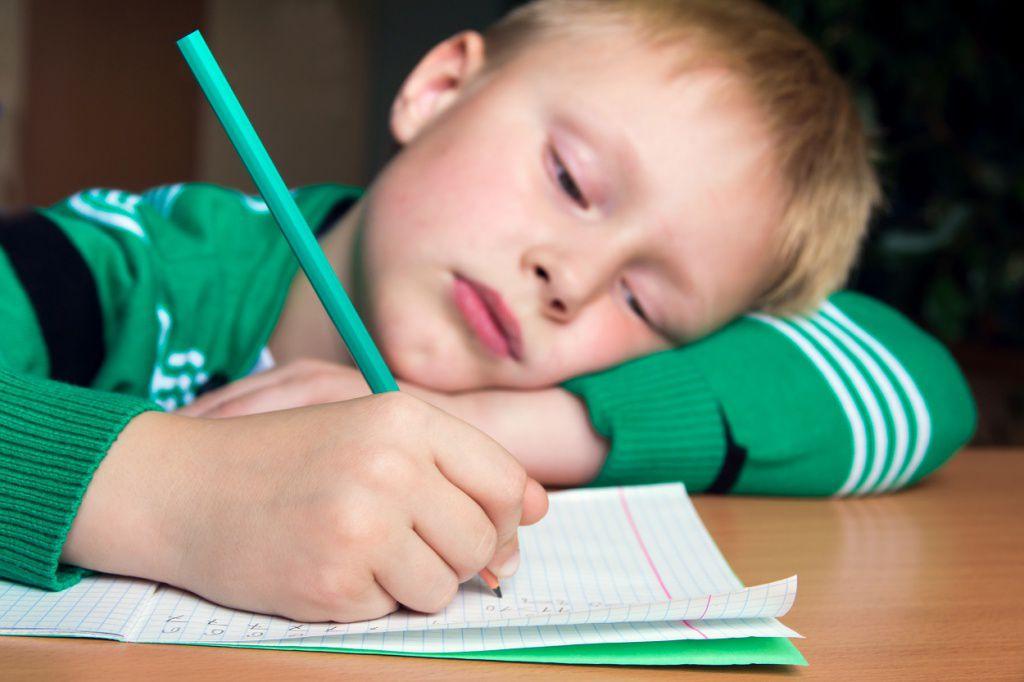 Уставший мальчик делает уроки