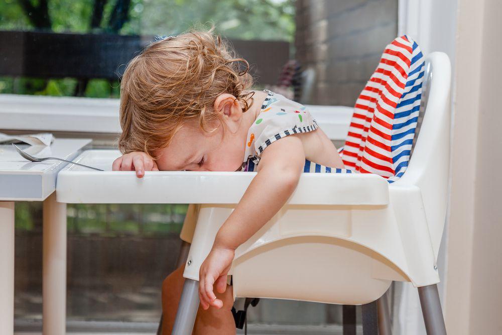 Грудной ребенок спит в детском стуле