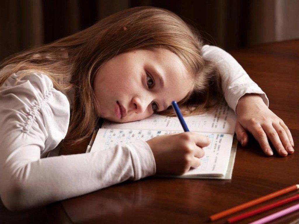 Уставшая девочка за письменным столом