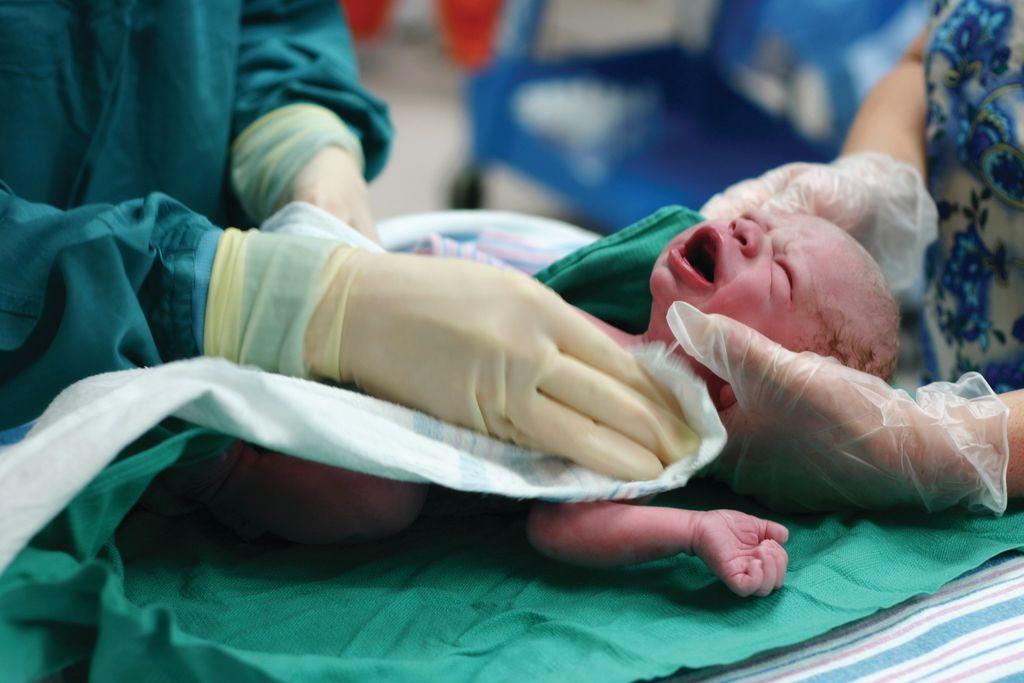 Кричащий новорожденный в руках у врачей