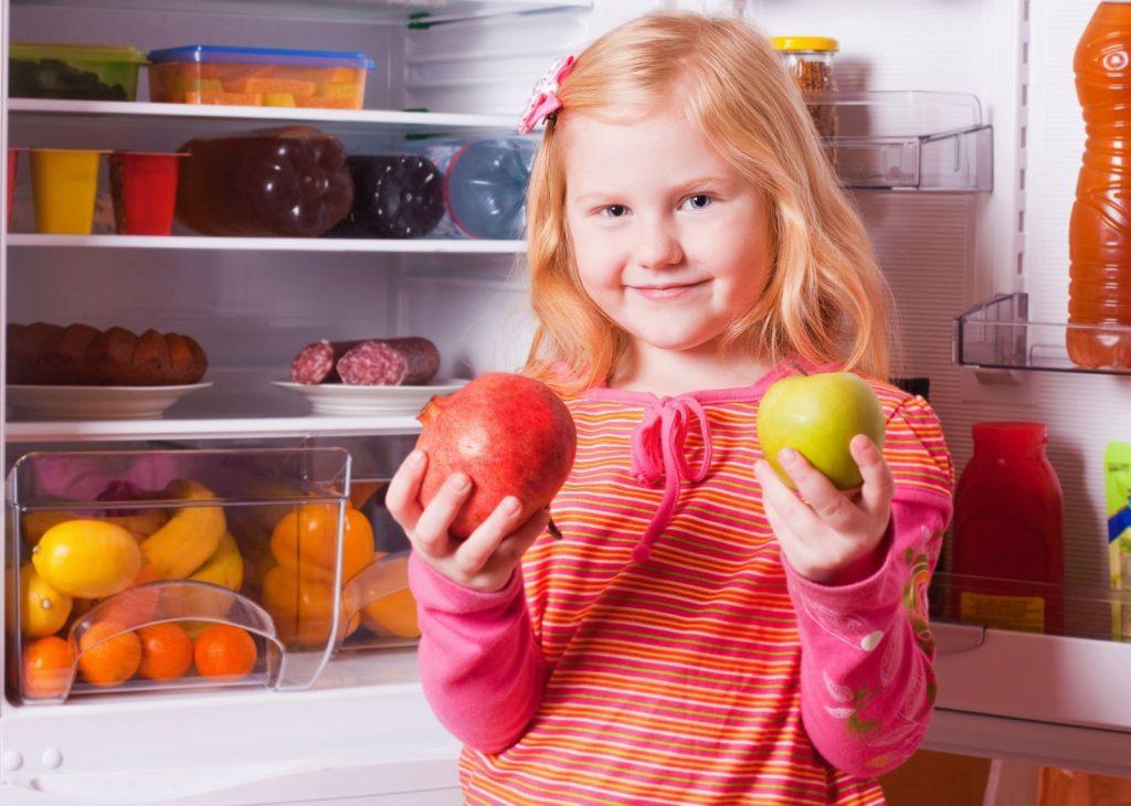 Девочка с яблоком и гранатом у отрытого холодильника