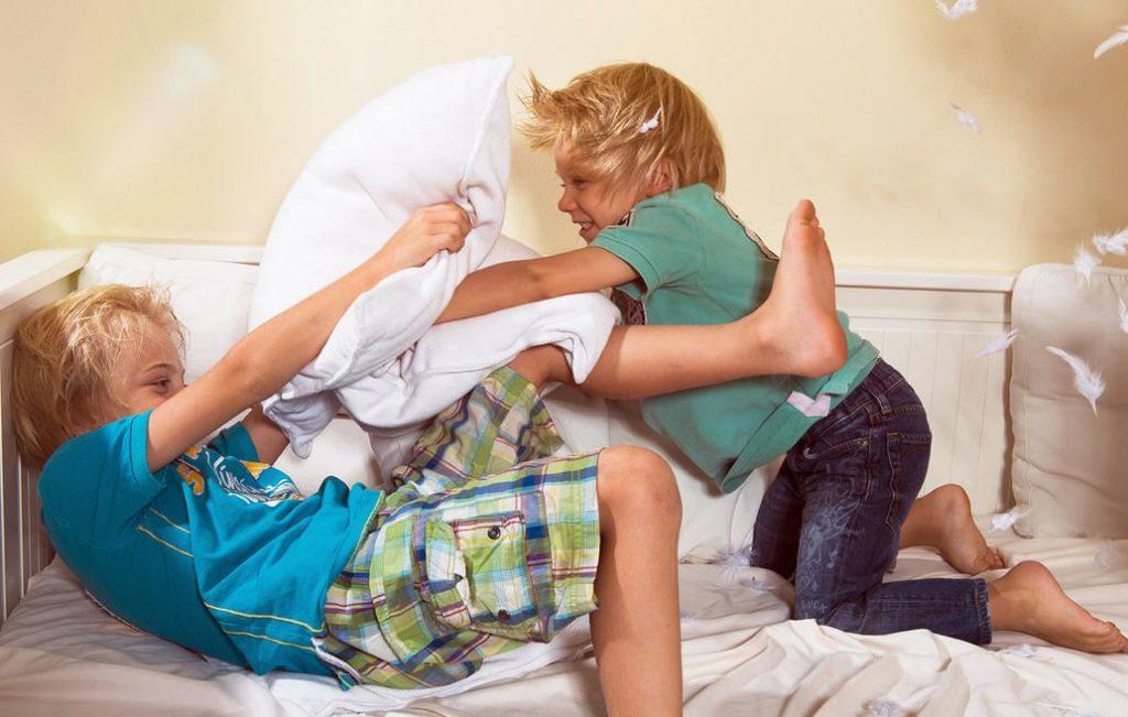 Мальчик бьет подушкой старшего брата
