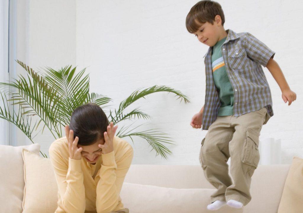 Мальчик прыгает на диване рядом с мамой