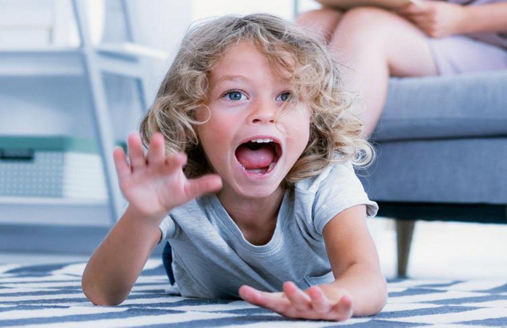 Мальчик ползет по полу и кричит