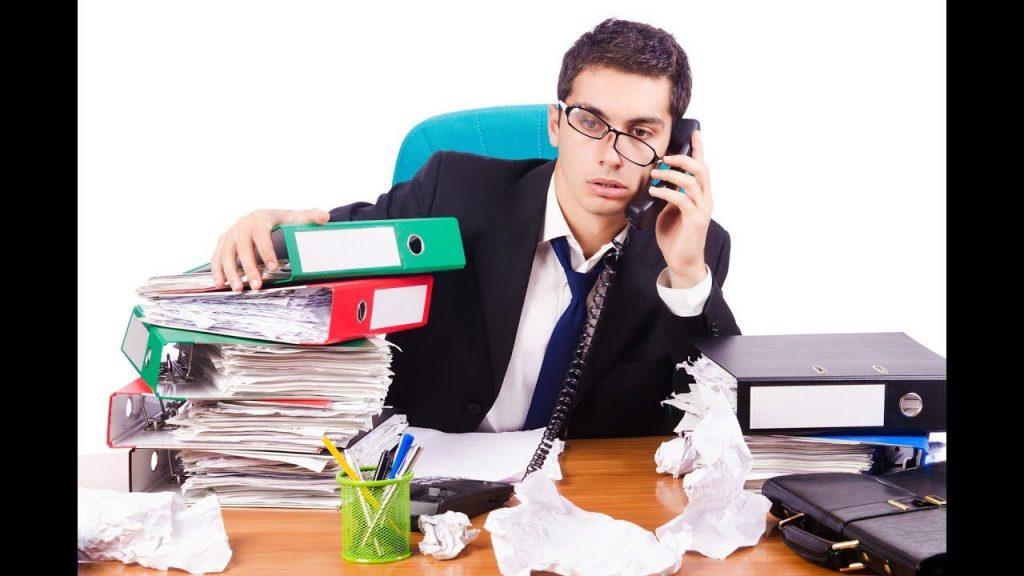 Загруженный работой молодой человек разговаривает по телефону