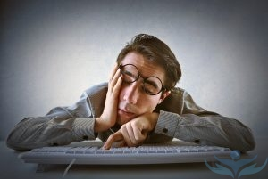 Уставший мужчина в очках перед клавиатурой